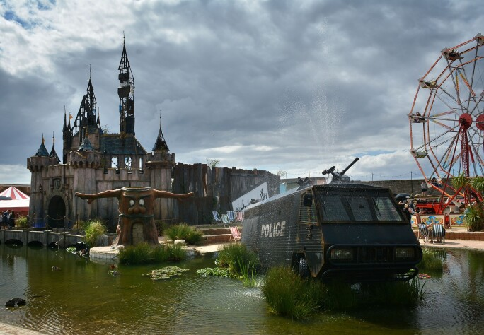 A fountain by Banksy, made from an abandoned police riot vehicle, is displayed in front of the fairy castle as Banksy's Dismaland Bemusement Park opens to the public, on August 28, 2015 in Weston-Super-Mare, England.