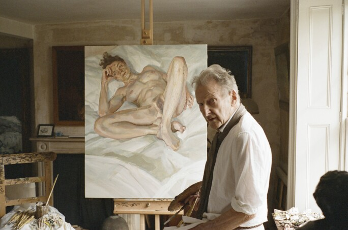 Lucian Freud standing in front of one of his nude portraits.