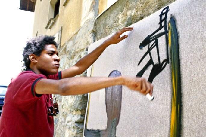 Photograph of Basquiat painting an outdoor wall in St. Moritz, Switzerland. He is wearing a