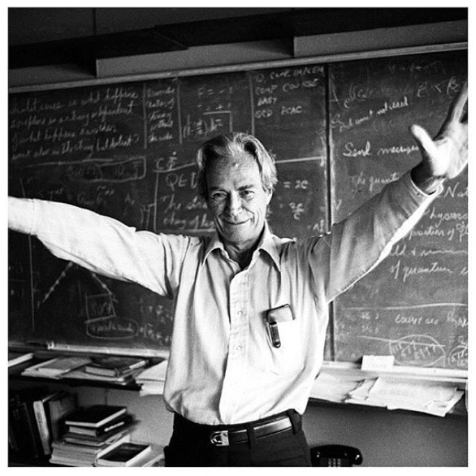 Richard Feynman in the classroom with his arms open and extended and standing in front of a blackboard covered in formulas.