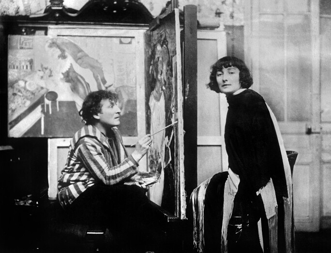 A black-and-white photograph of Marc Chagall painting his wife Bella Rosenfeld in his workshop in Paris, 1926.