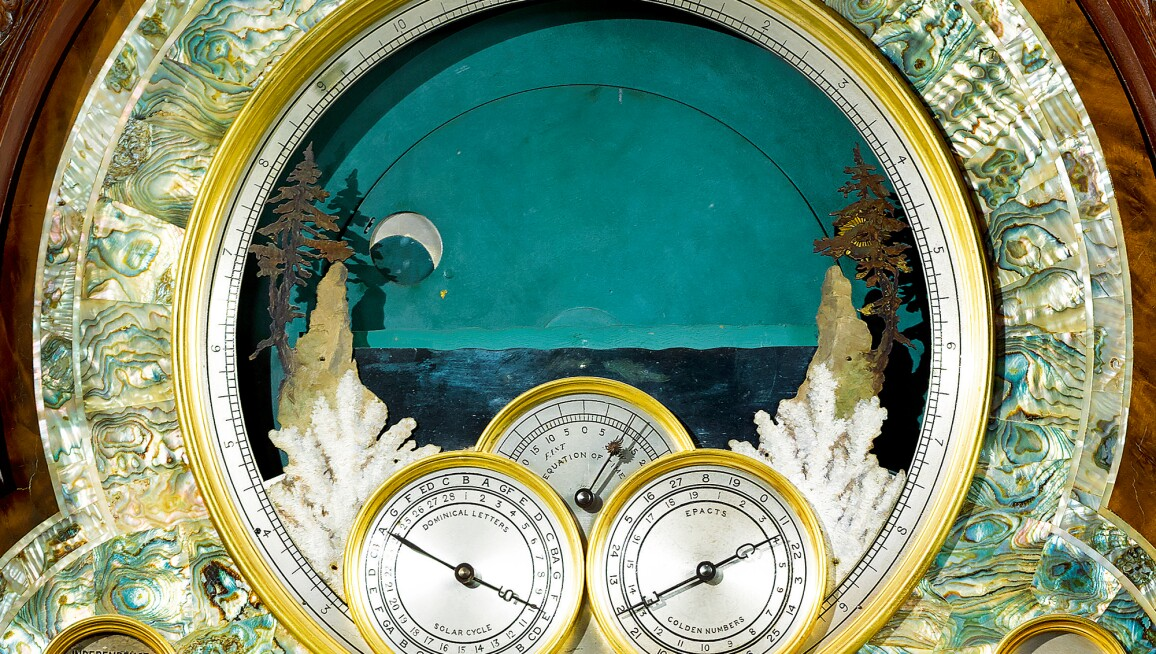 Close-up image of the clock face, featuring a lake at dusk.