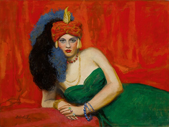 Blonde woman in a green dress wearing a red turban, posing in front of a red background.