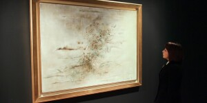 woman standing in front of zao wou ki's abstract painting
