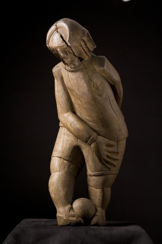 Christ Playing Football, wooden sculpture.