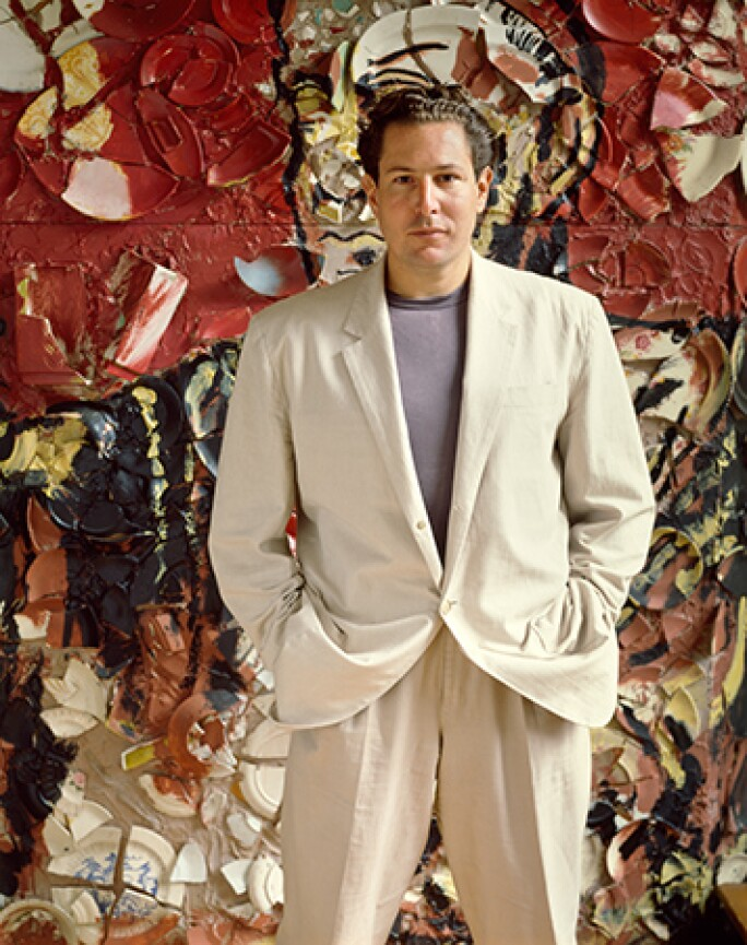 Julian Schnabel in a white suit standing in front of one of his canvases.