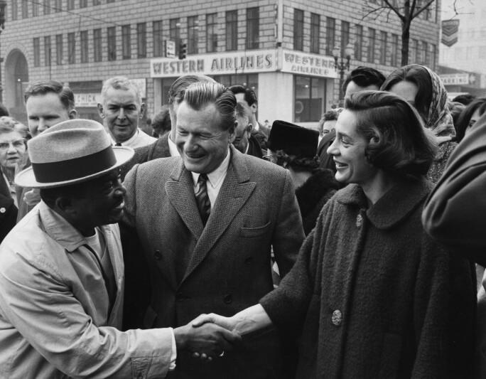 Happy Rockefeller shaking a man's hand