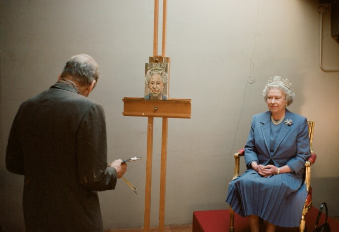A photograph of Her Majesty Queen Elizabeth II in a slate gray suit, having her portrait painted.