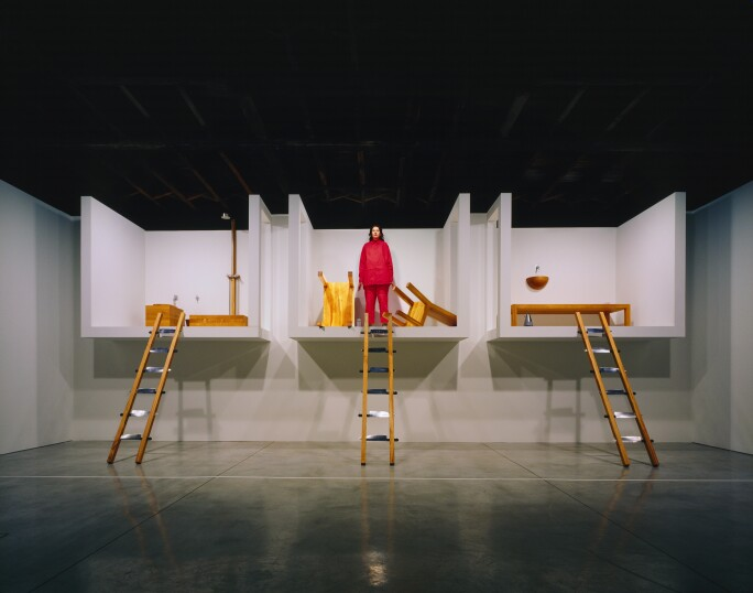 Marina Abramović dressed in red standing in one of three elevated rooms during her performance piece at Sean Kelly gallery in New York in 2002.jpg