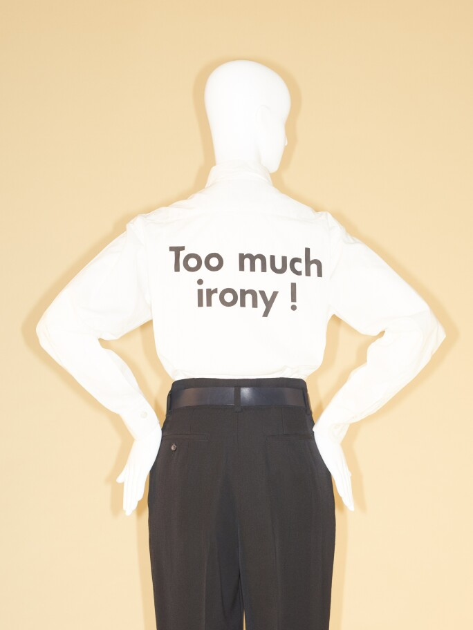 "Moschino shirt in white with the words ""Too Much Irony"" written on the back."