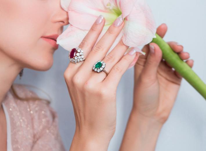 une femme portant des bagues en émeraude, diamants et rubis dans une vente aux enchères de bijoux fins en consignation