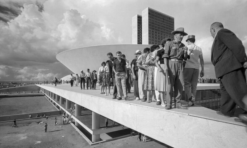 Populares sobre cobertura do palácio do Congresso Nacional no dia da inauguração de Brasília, Distrito Federal, 1960 (People on the esplanade of the National Congress on inauguration day of Brasília, Federal District)