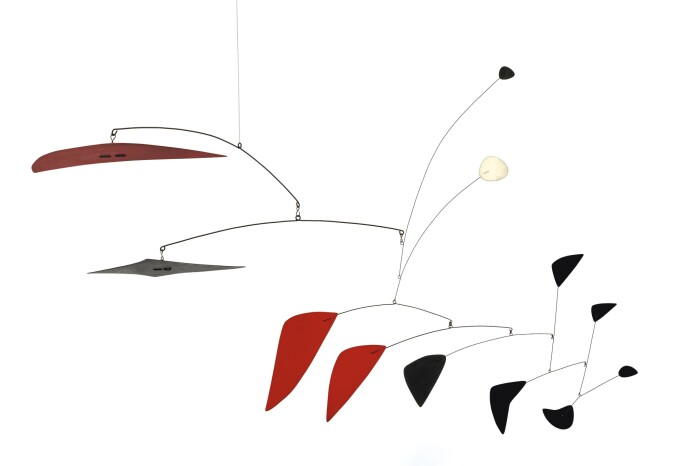 A mobile with red, black a one white geometric shapes.