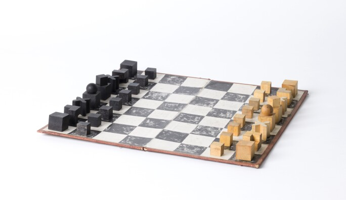 Bauhaus-style chess set with wooden pieces atop of chess board