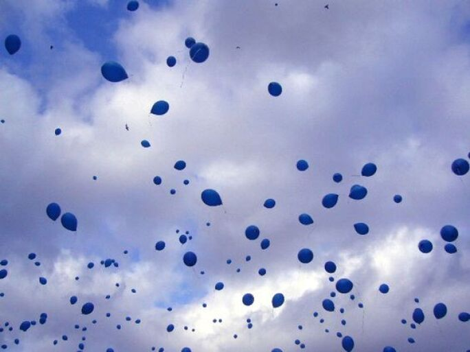 Blue balloons floating in a cloudy blue sky